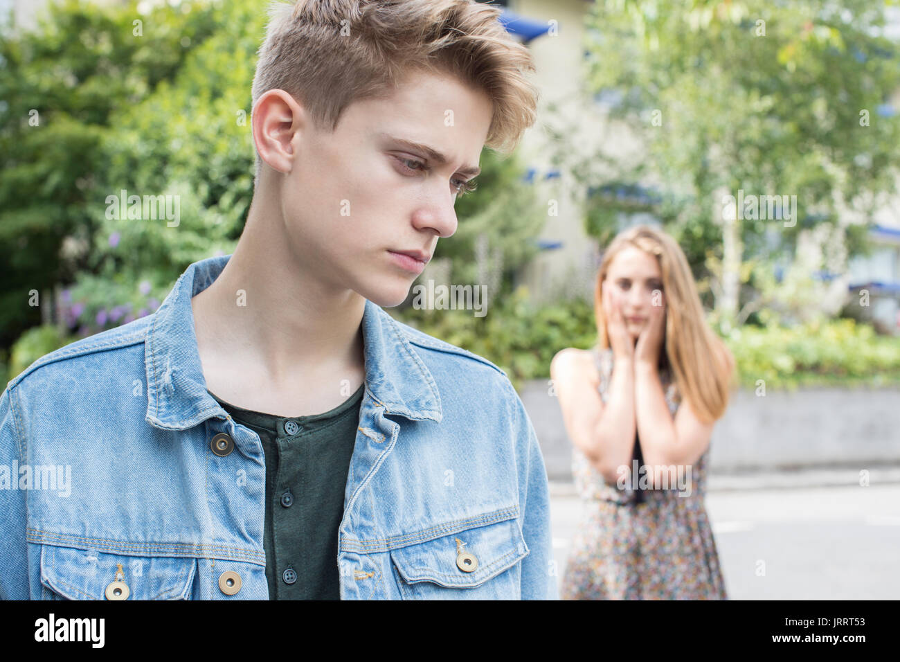 Unhappy Teenage Couple With Relationship Problem In Urban Setting - Stock Image