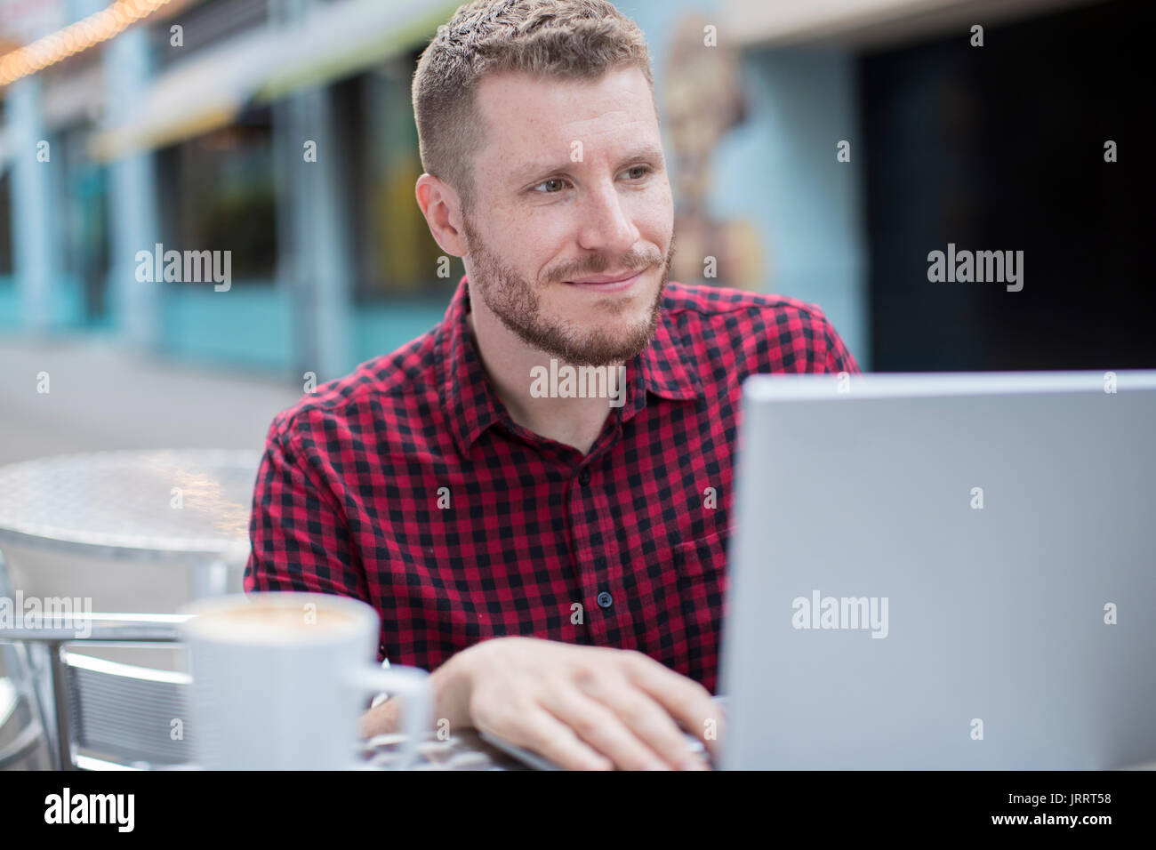 Young Man At Outdoor Cafe Working On Laptop - Stock Image