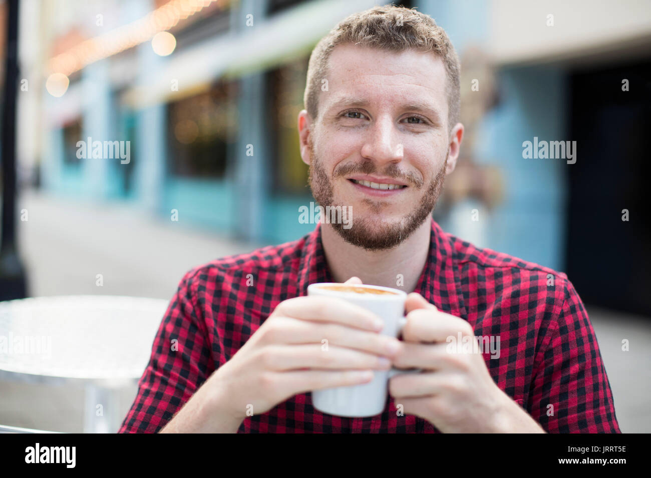 Portrait Of Young Man Drink Coffee At Outdoor Cafe Table - Stock Image