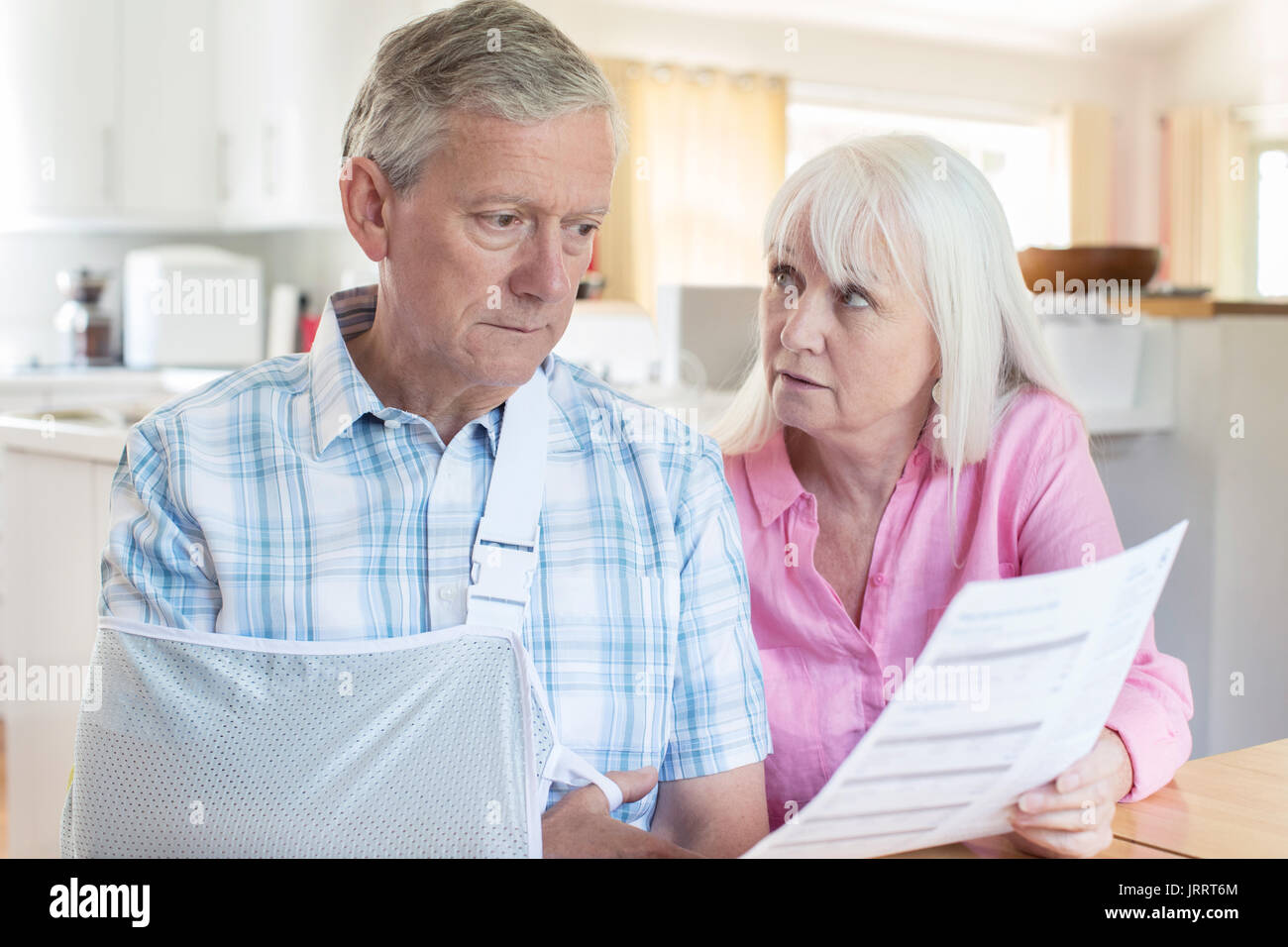 Couple Reading Letter About Husband's Injury - Stock Image