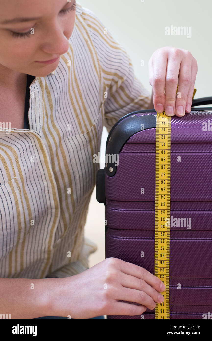 Close Up Of Woman Measuring Suitcase Before Holiday - Stock Image