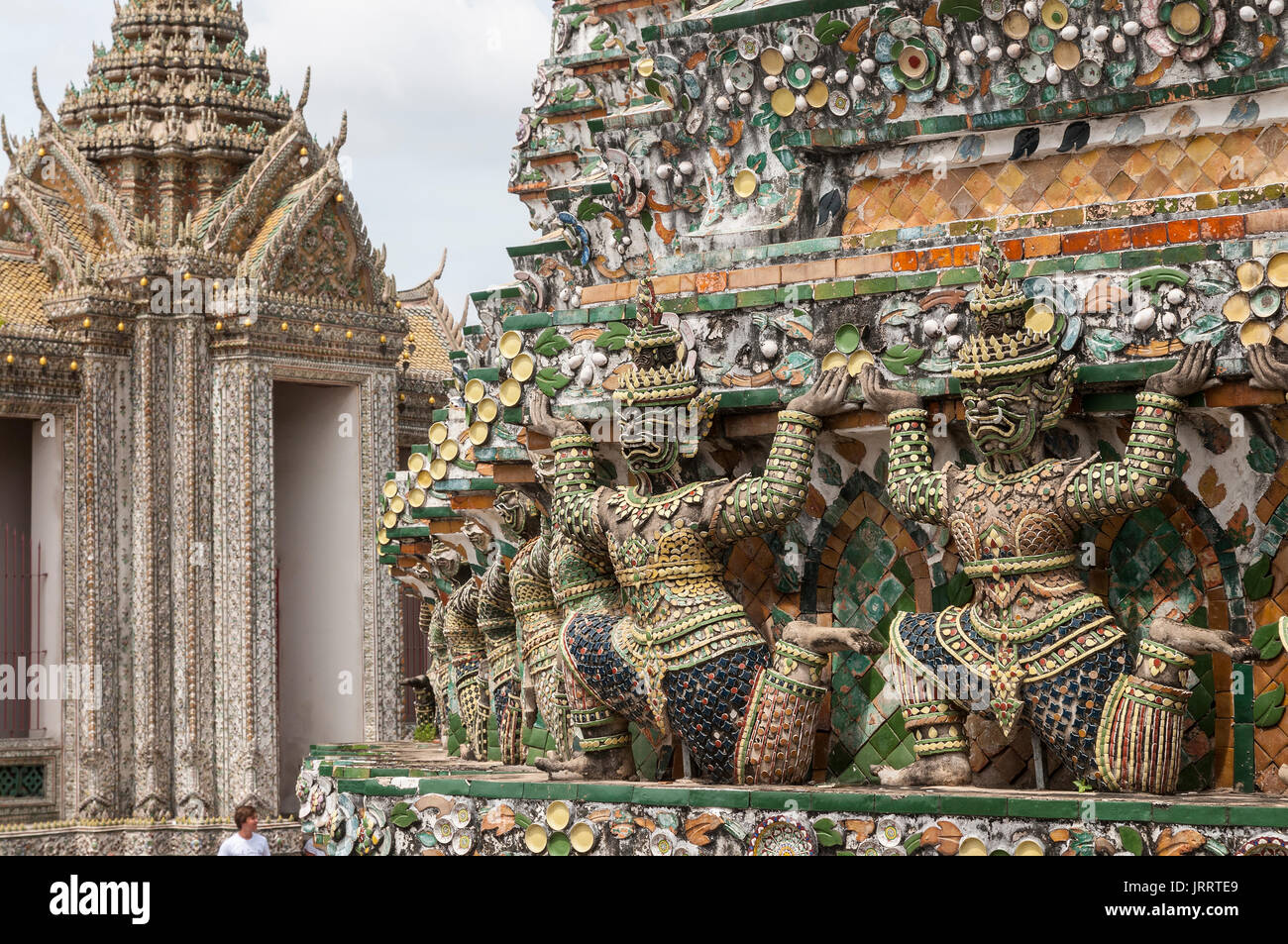 Ancient Chinese figures decorated with ceramic tiles,  at the Wat Arun temple, on the Chao Phraya River. Yai district, Bangkok, Thailand - Stock Image