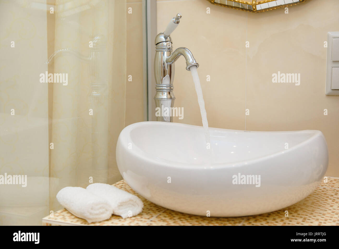 Water pours out of the tap. Modern bathroom interior. - Stock Image