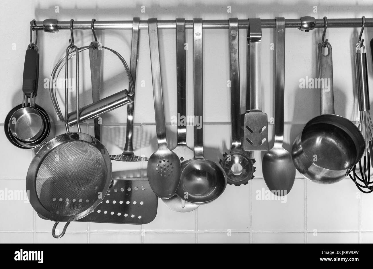 Various kitchen utensils haning from a rack - Stock Image