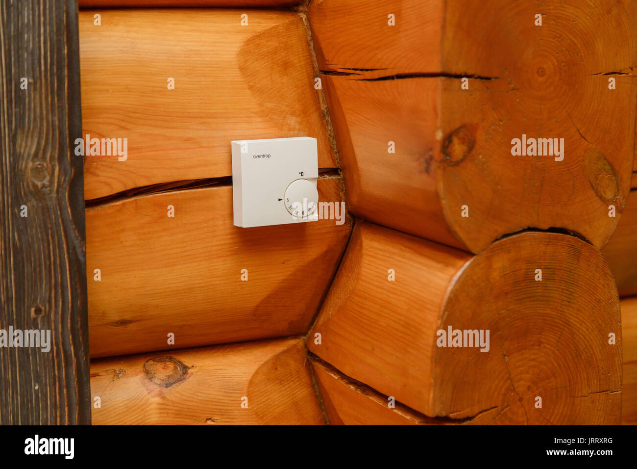 Room temperature controller for heating and cooling on a wall in a wooden house - Stock Image