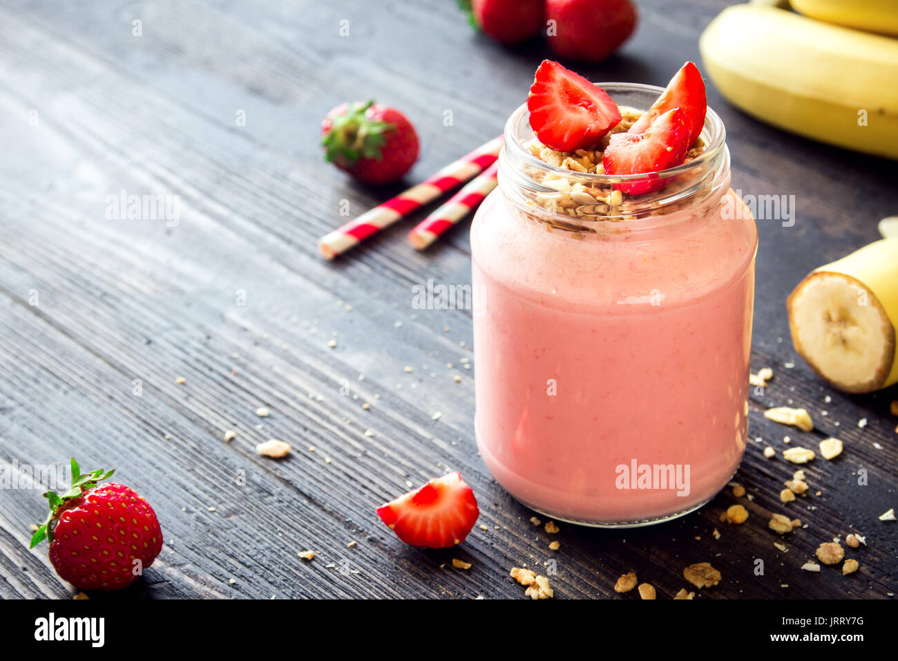 Strawberry and banana smoothie with homemade granola. Healthy breakfast or snack. Banana and strawberry smoothie in glass jar. - Stock Image