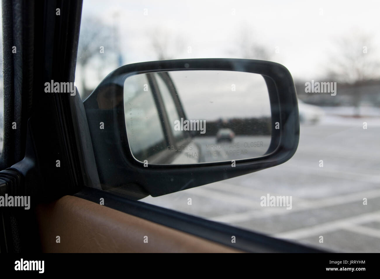 View of wing mirror reading 'Objects in mirror are closer than they appear', on parked car. - Stock Image