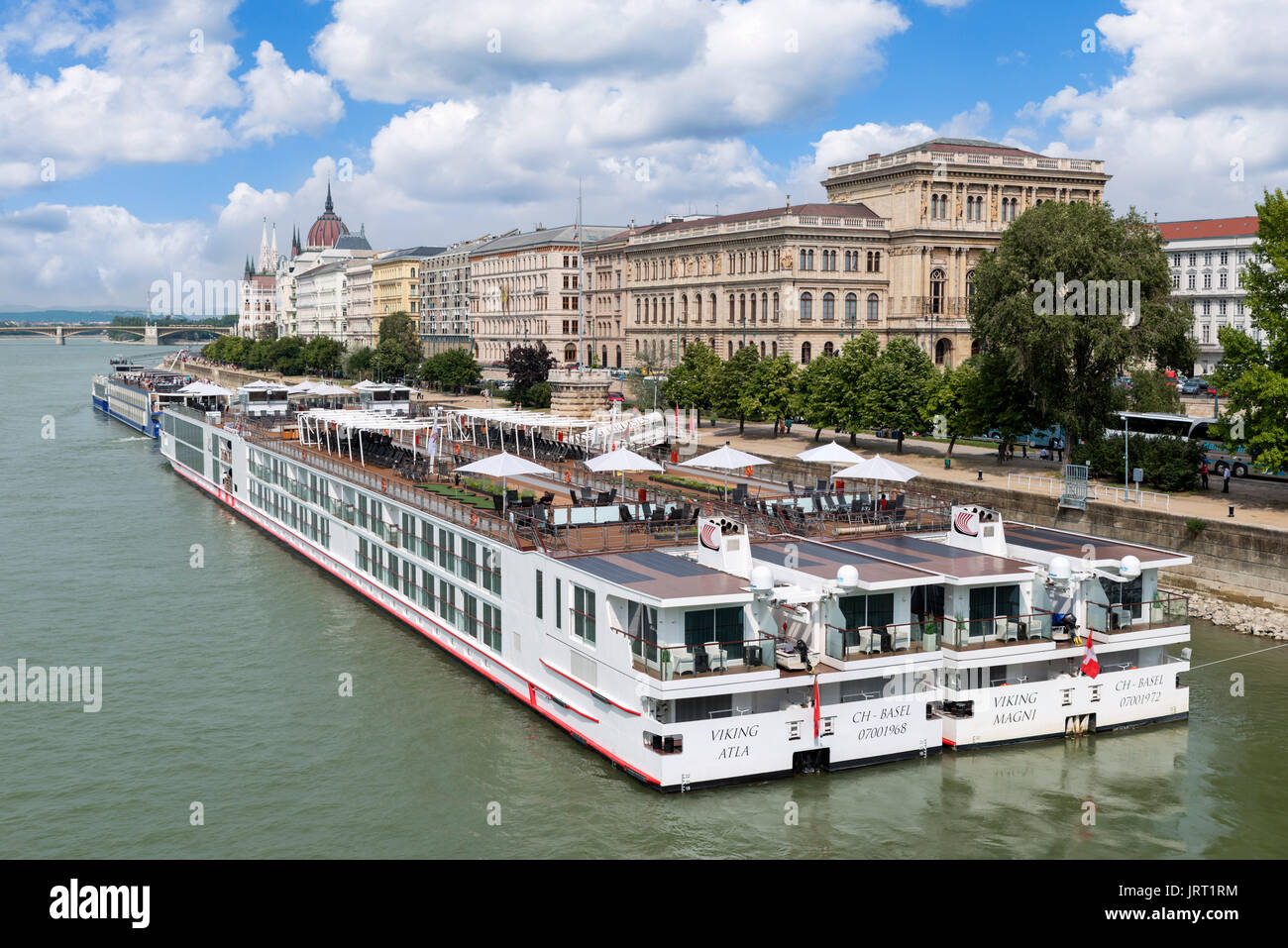 Viking River Cruises cruise boats moored on the Pest side of the river Danube with the Parliament building in the distance, Budapest, Hungary - Stock Image