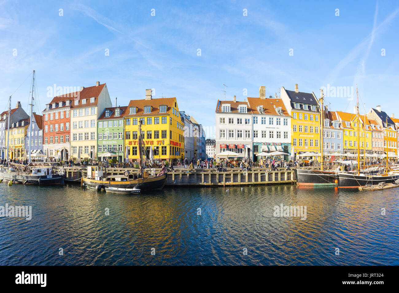 Copenhagen, Denmark - May 1, 2017: Nyhavn with its picturesque harbor with old sailing ships bobbing on the canals' water, and colourful facades of ol - Stock Image