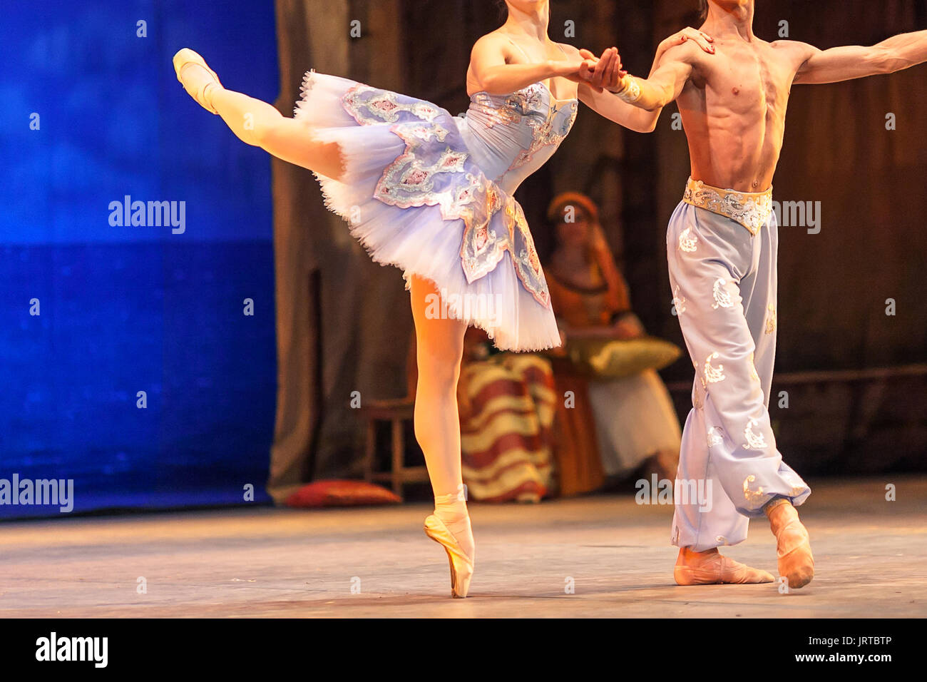 ballet, love, theater concept. dance duet of two persons, ballerina like porcelain statuette standing on one stretched toe and holding on to her tough male partner - Stock Image