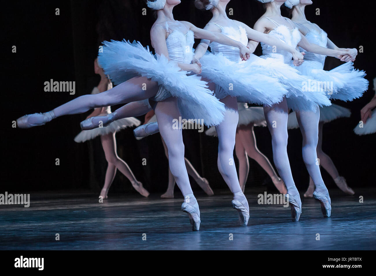 beauty, agility, dancing concept. arm in arm four elegant and graceful female ballet dancers, playing the roles of petite swans, moving, dancing and jumping synchronously - Stock Image