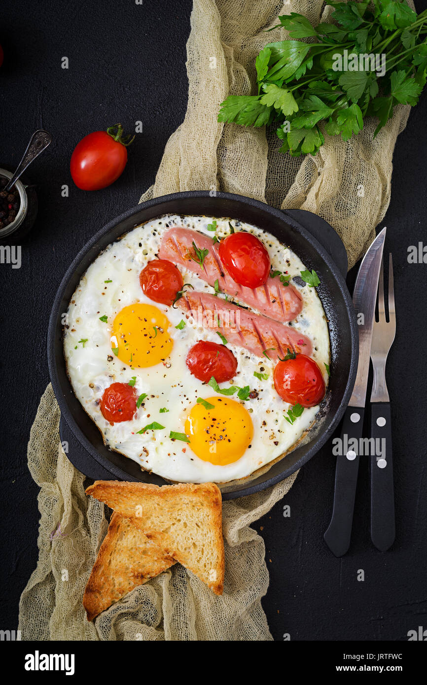 English breakfast - fried egg,  tomatoes and sausage. Top view. Flat lay - Stock Image
