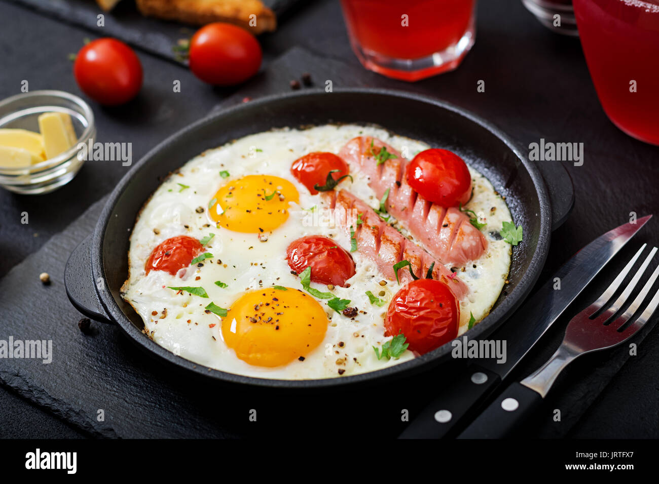 English breakfast - fried egg,  tomatoes and sausage. - Stock Image