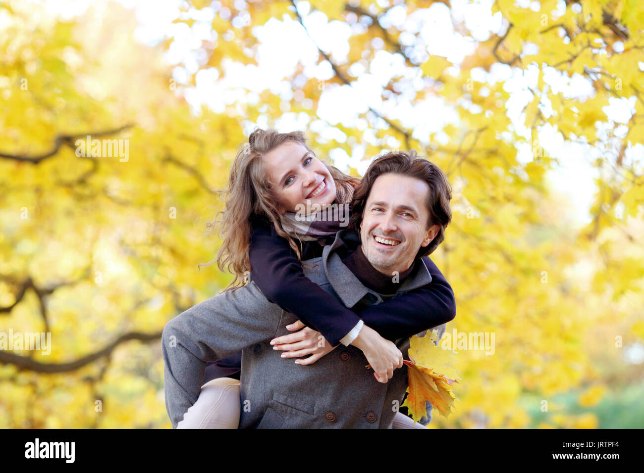 Love, relationships, season and people concept - happy young couple having fun in autumn park piggyback ride - Stock Image