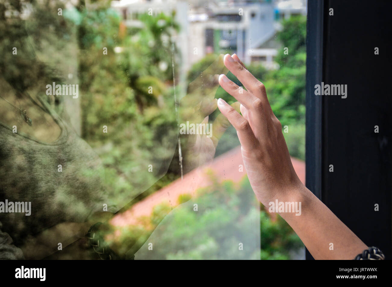 Reflection of a human hand touching a glass window showing the concept of longing and sadness - Stock Image