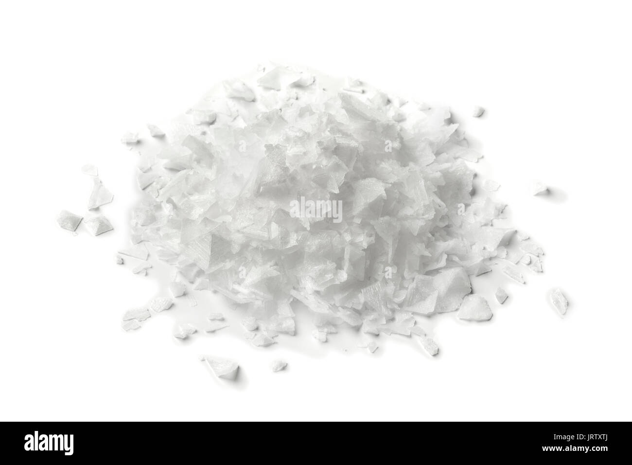 Heap of salt flakes on white background - Stock Image