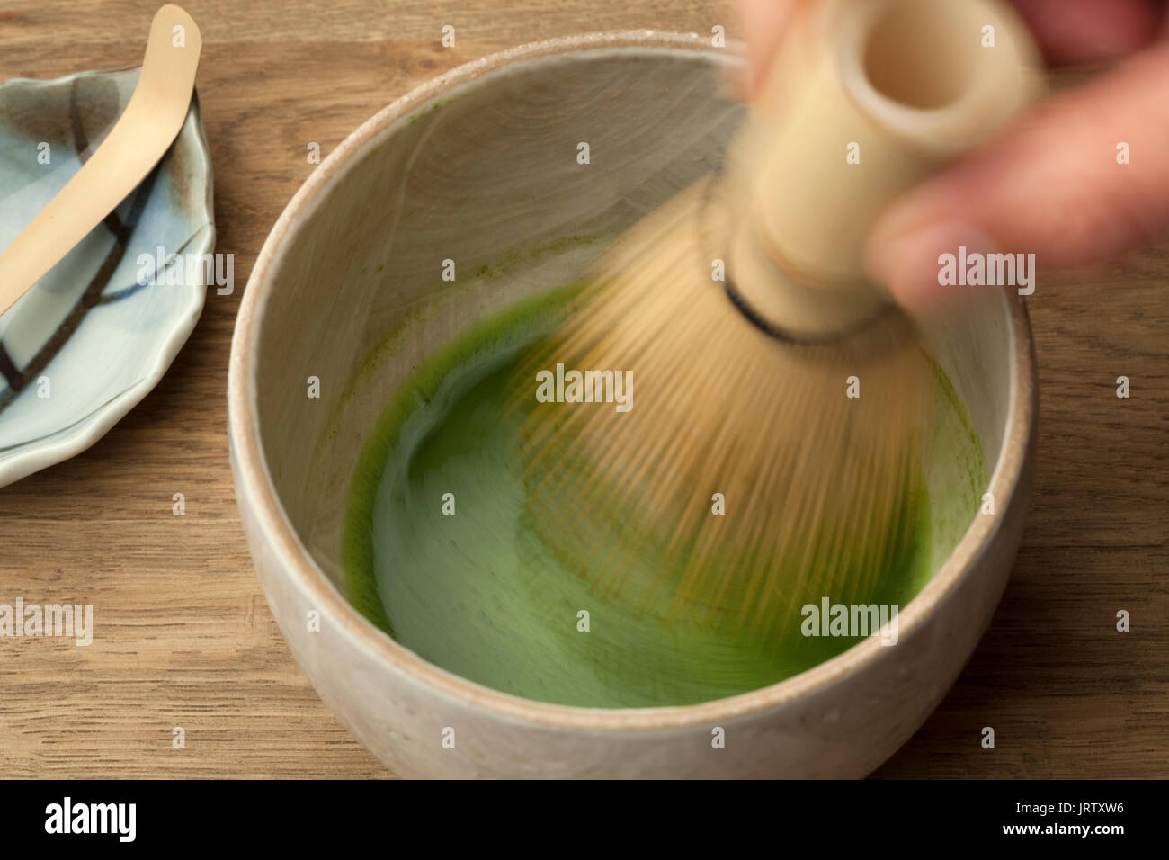 Preparing a bowl of matcha tea with a tea whisk - Stock Image