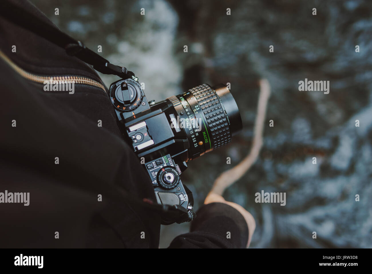 Vintage film camera around woman neck while she holds a stick into a river. - Stock Image
