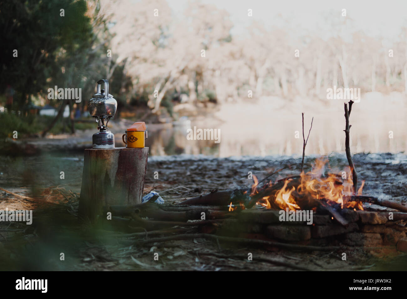 Morning campfire by the Murray River in the golden light with the camp stove making a coffee. - Stock Image