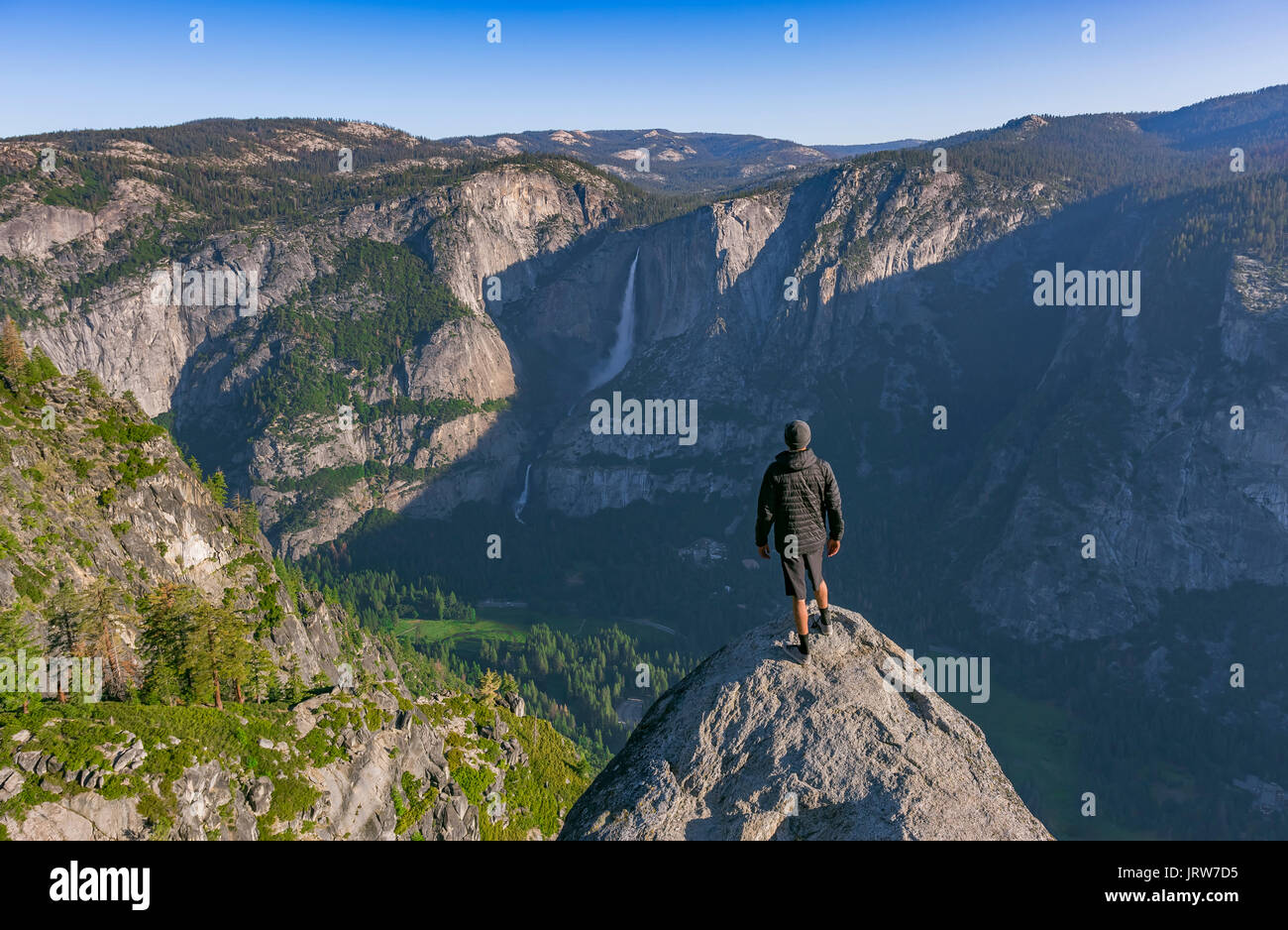 Panoramic views from Glacier Point of Yosemite Falls. Standing on a cliff and looking down at the valley at sunrise Stock Photo