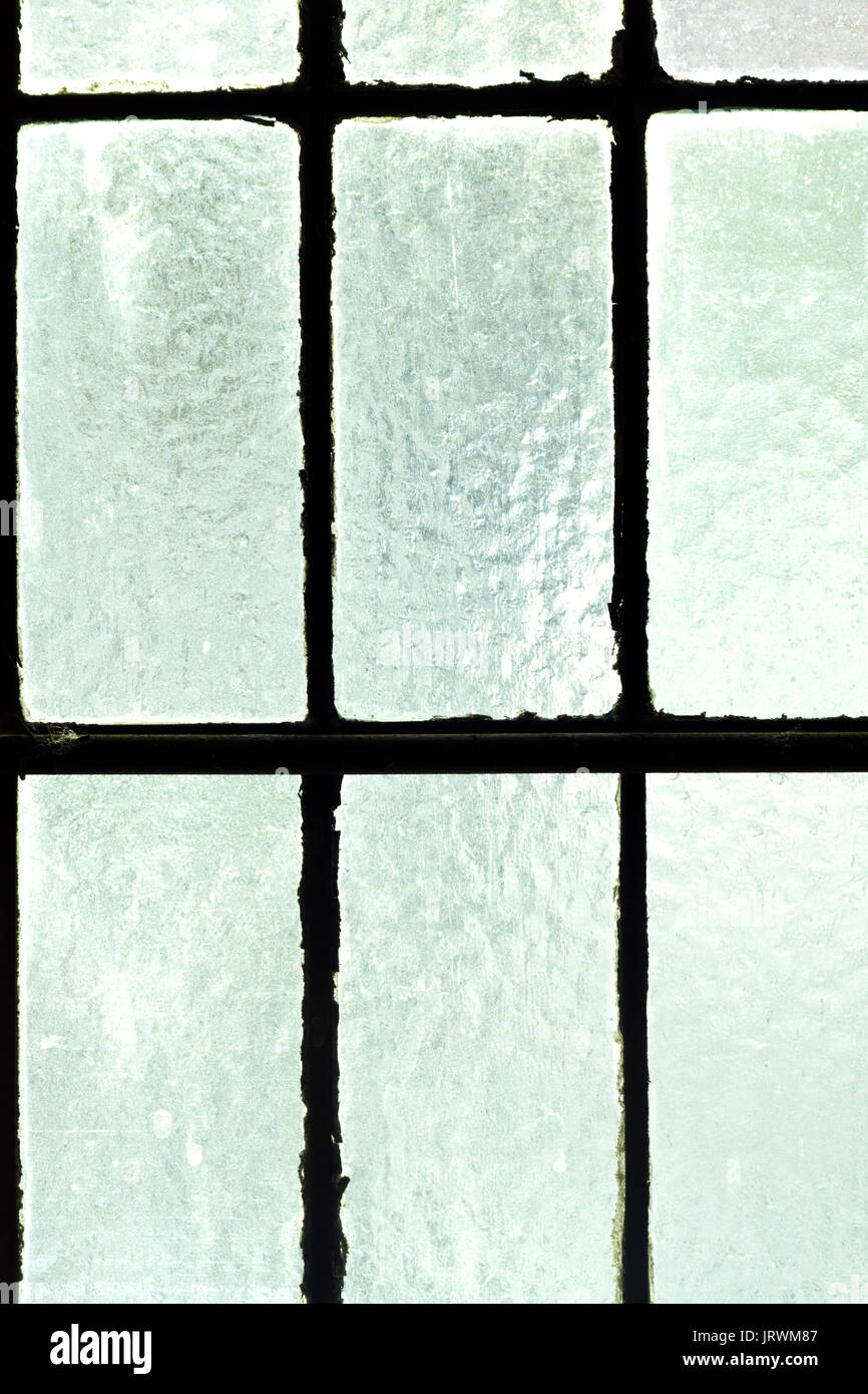 Close up of old window with green frosted glass panes from inside - Stock Image