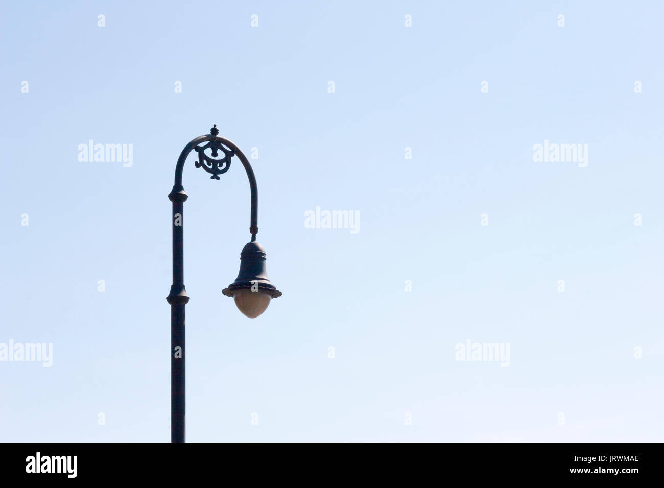 Elegant lamppost isolated against a cloudless pale blue sky - Stock Image