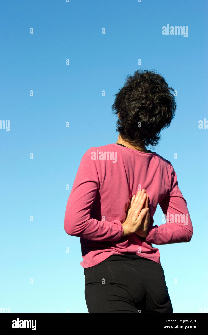 Woman doing yoga outside hands behind back - Stock Image