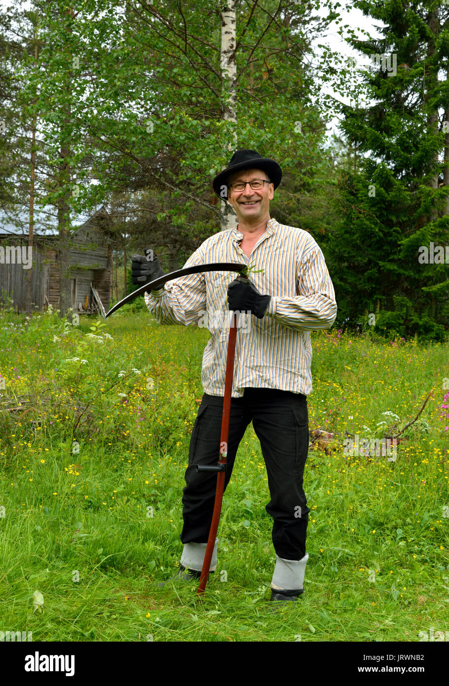 Middle-aged Farmer in old vintage clothes mows grass on lawn traditional  wooden scythe c72f301524d6