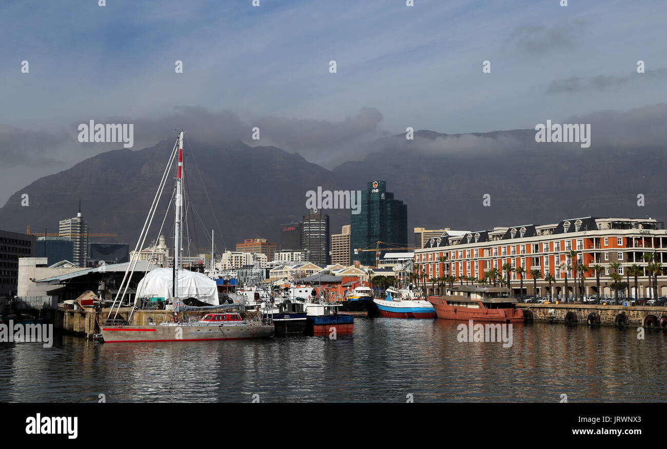 A view of the V&A Waterfront with clouds over Table Mountain and Devil's Peak in the background in Cape Town, Western Cape, South Africa. - Stock Image