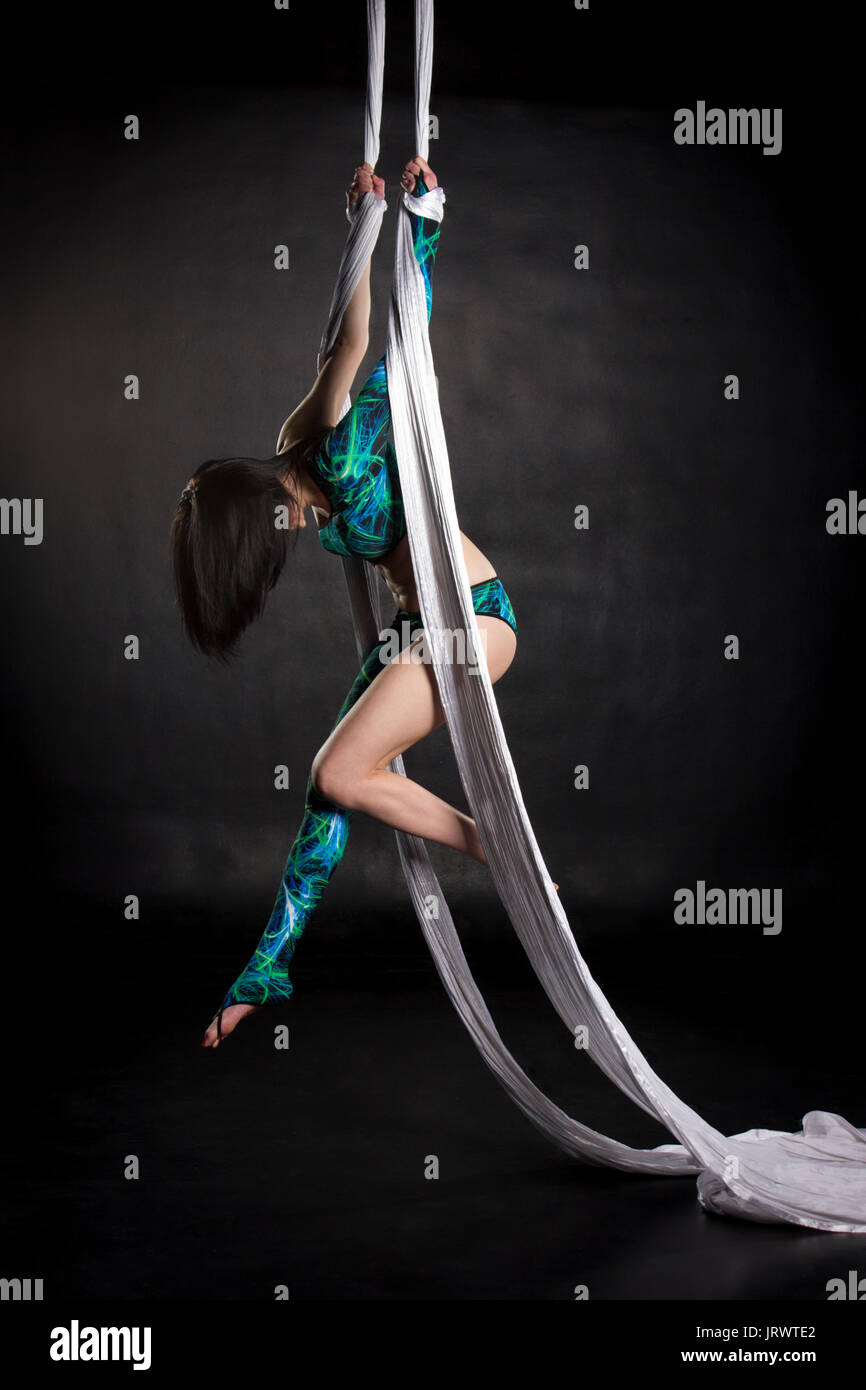 Aerialist woman doing some flexibility and strength tricks on silks - Stock Image