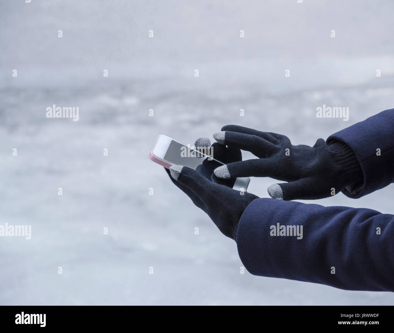 Girl's hands, in special gloves for typing on a gadget in winter, close-up - Stock Image