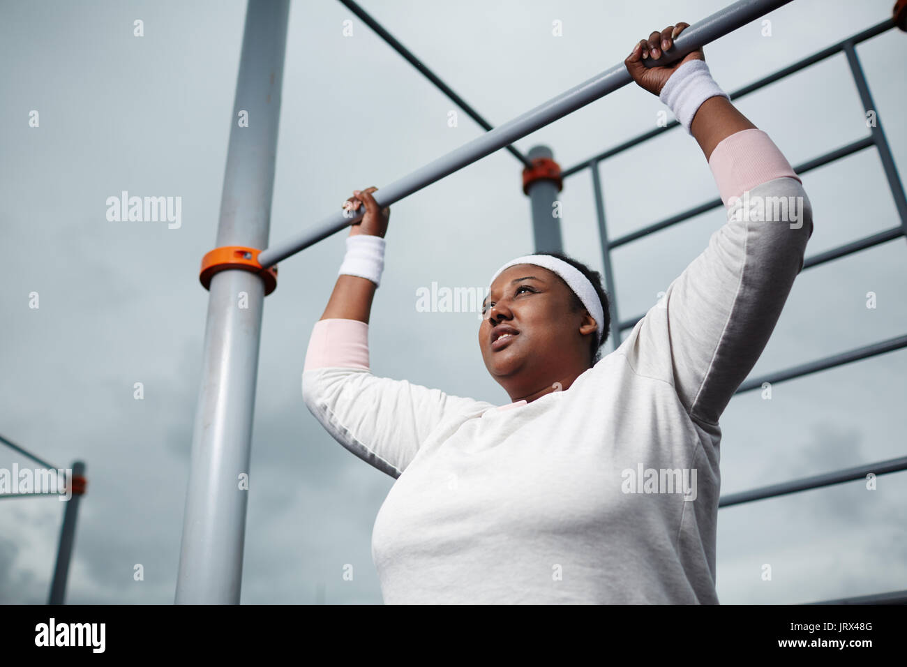 Determined overweight African woman practicing pull-up exercise outdoors - Stock Image
