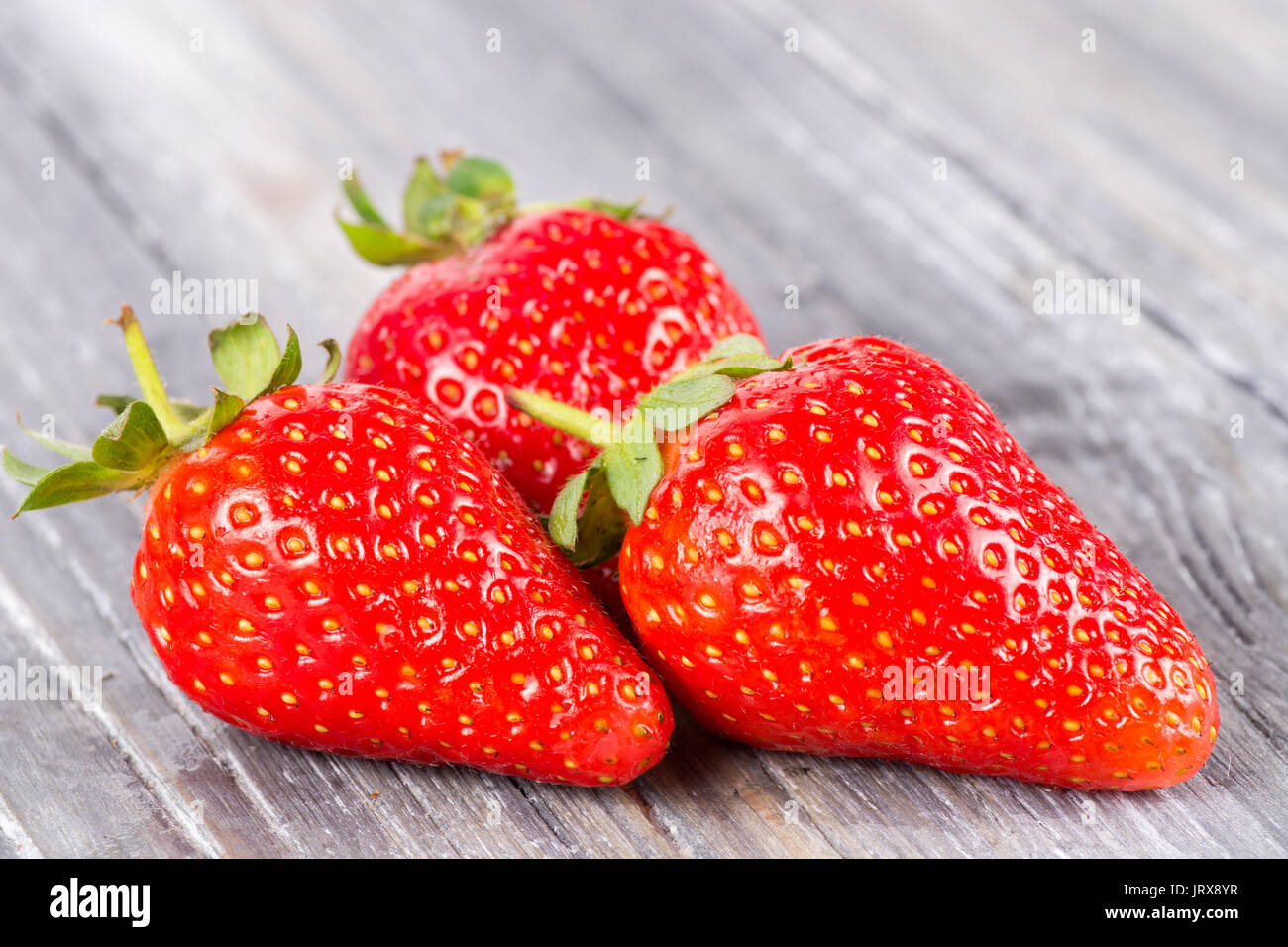 strawberries on wooden background fresh and ripe - Stock Image