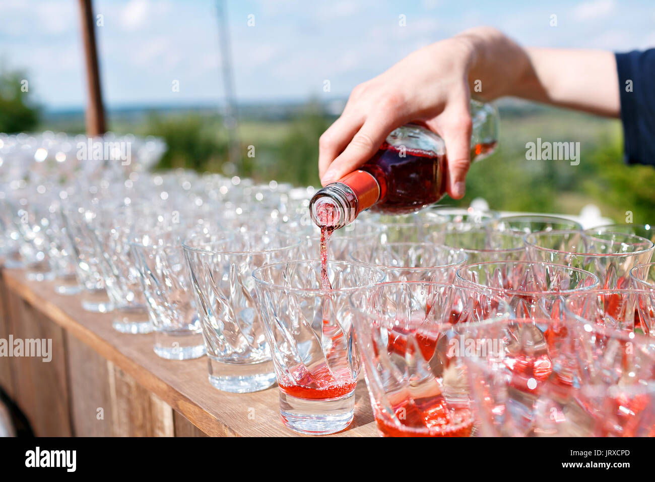 Bartender pouring cocktail in glasses - Stock Image