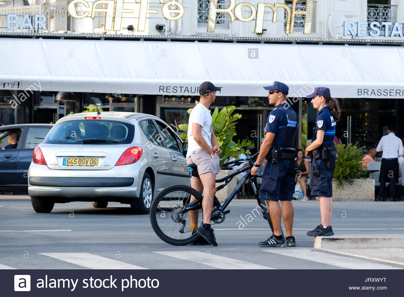 Two French police officers ask to check. Males pockets as part of the heightened security state in France - Stock Image