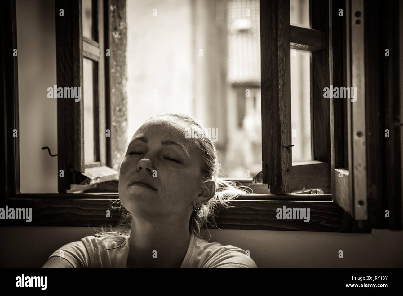 pensive young woman with closed eyes lost in thoughts relaxing and dreaming near opened  window in black and white color in vintage style with dramati - Stock Image
