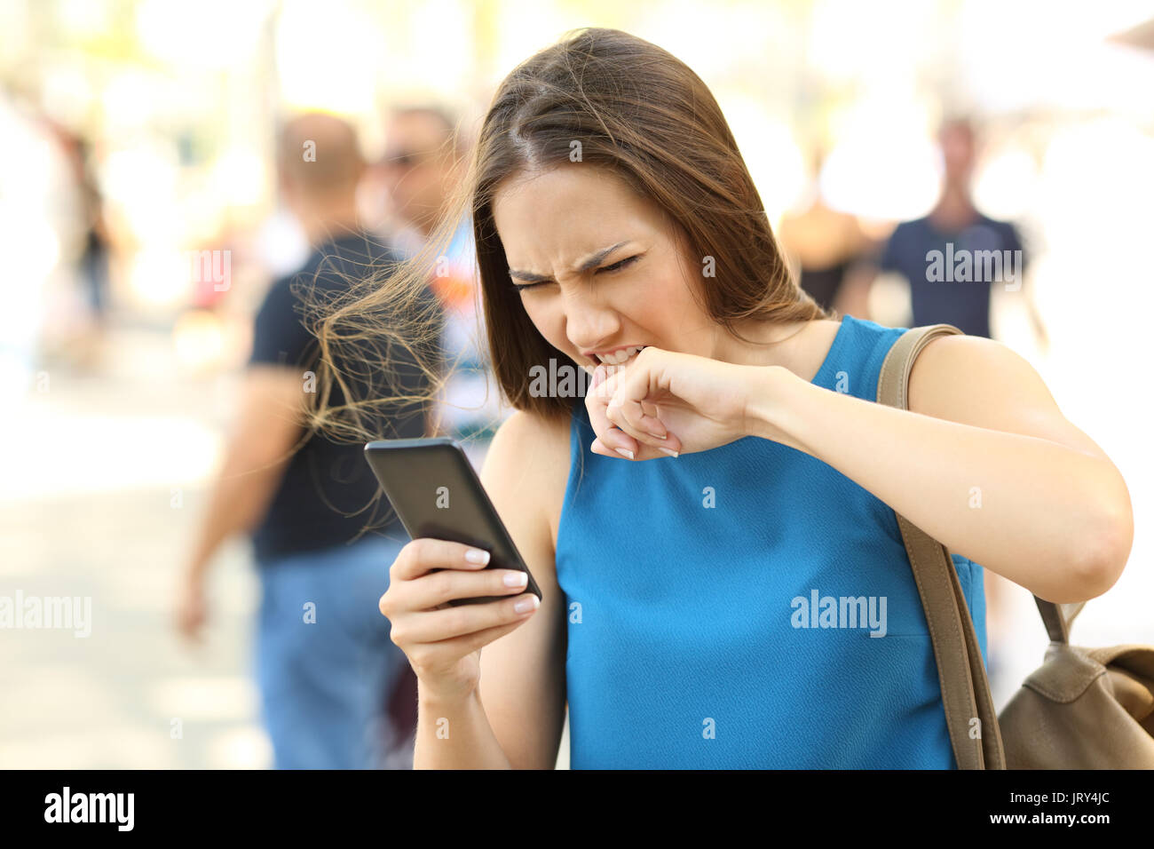 Angry woman fed up of her mobile phone on the street - Stock Image