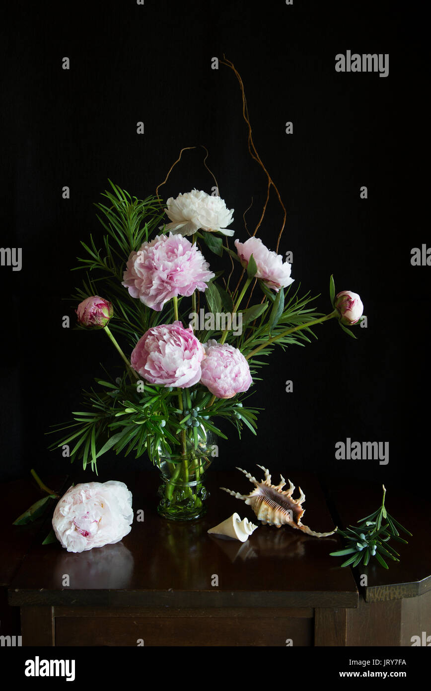 Peonies in a Dutch Roemer style wine glass in natural light arranged with Lambdis scorpius and Thatcheria mirabilis - Stock Image