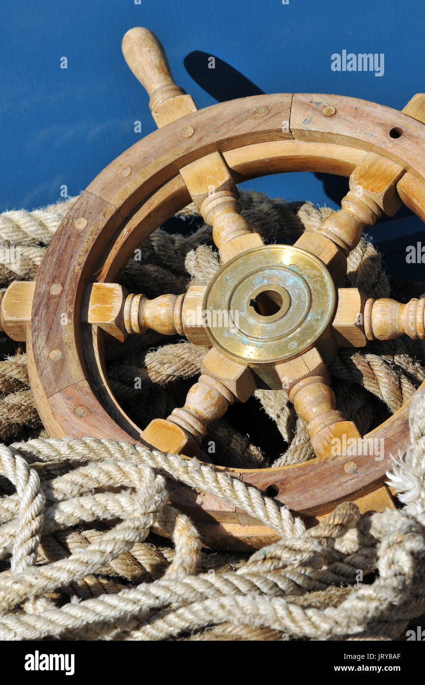 a ships wheel helm and some rope in a nautical or coastal setting old and weather beaten maritime nautical setting - Stock Image