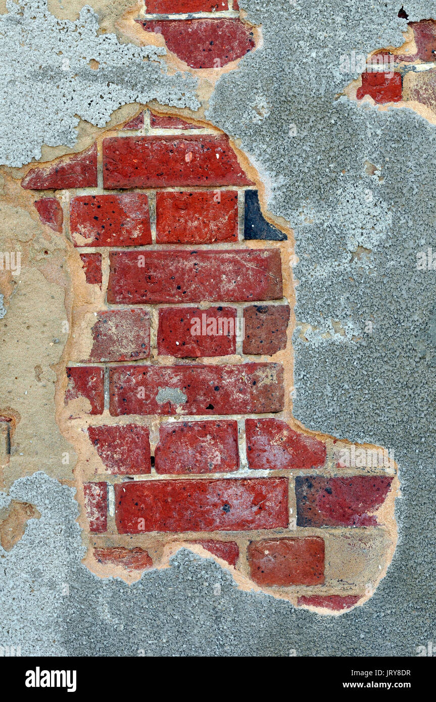 Mortar or render falling off of a wall crumbling away in a state of disrepair dereliction walls and brickwork repairs on a building maintenance lack. - Stock Image