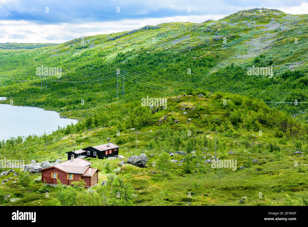 Group of small lakeside cabins in mountainous landscape powerlines on the mountainside mountain peak in background location hardangervidda in norwa