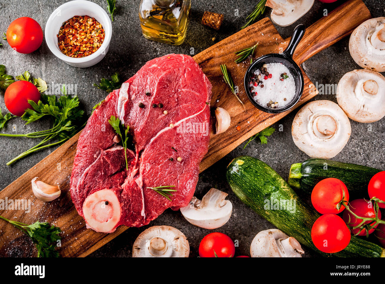 Raw meat with ingredients for dinner. Beef fillet, tenderloin, on cutting board, with salt, pepper, parsley, rosemary, oil, garlic, tomato, mushroom,  - Stock Image
