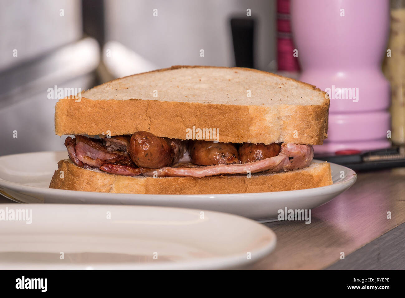 Sausage and bacon sandwich on white bread Stock Photo