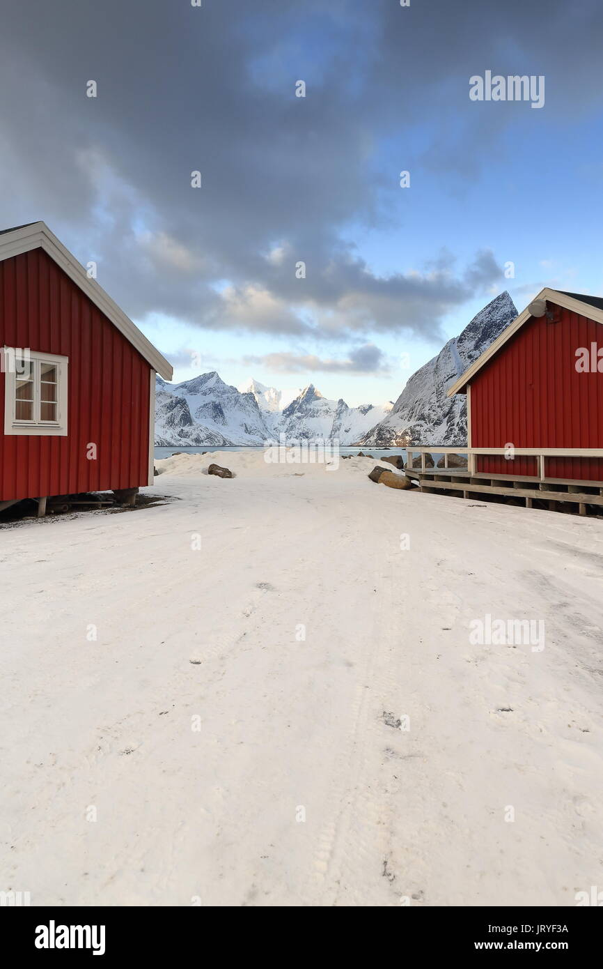 Red wooden rorbuer-traditional seasonal fishing huts-now for tourist use-built with one end on poles in the water. Mounts around Forsfjorden-Kjerkfjor - Stock Image