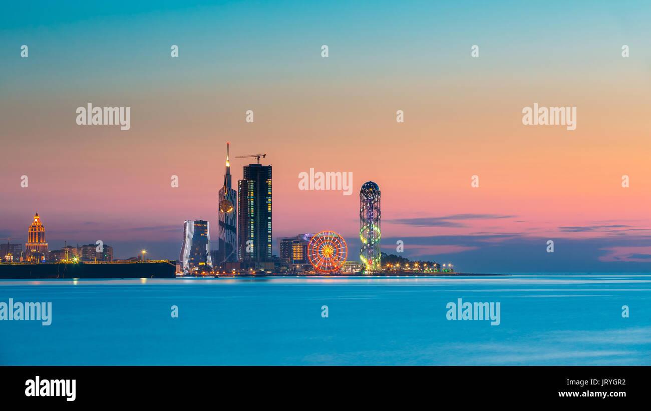 Batumi, Adjara, Georgia - May 25, 2016: Panorama of illuminated resort town at sunset. Radisson Blu Hotel, Black Stock Photo