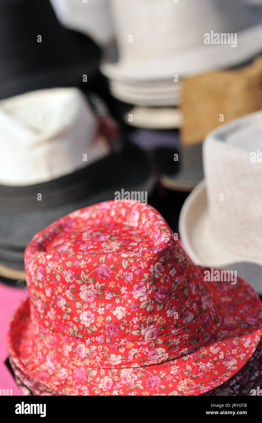 a selection variety of hats for sale trilbys and Stetsons caps and berets pork pies and bowlers at a fair or in the market pace stalls - Stock Image