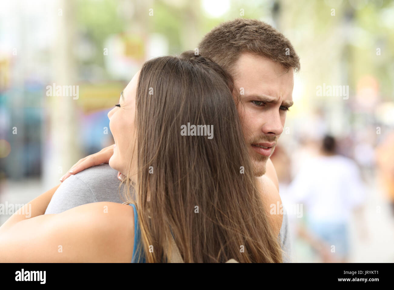 Discontent boyfriend hugging his partner on the street - Stock Image