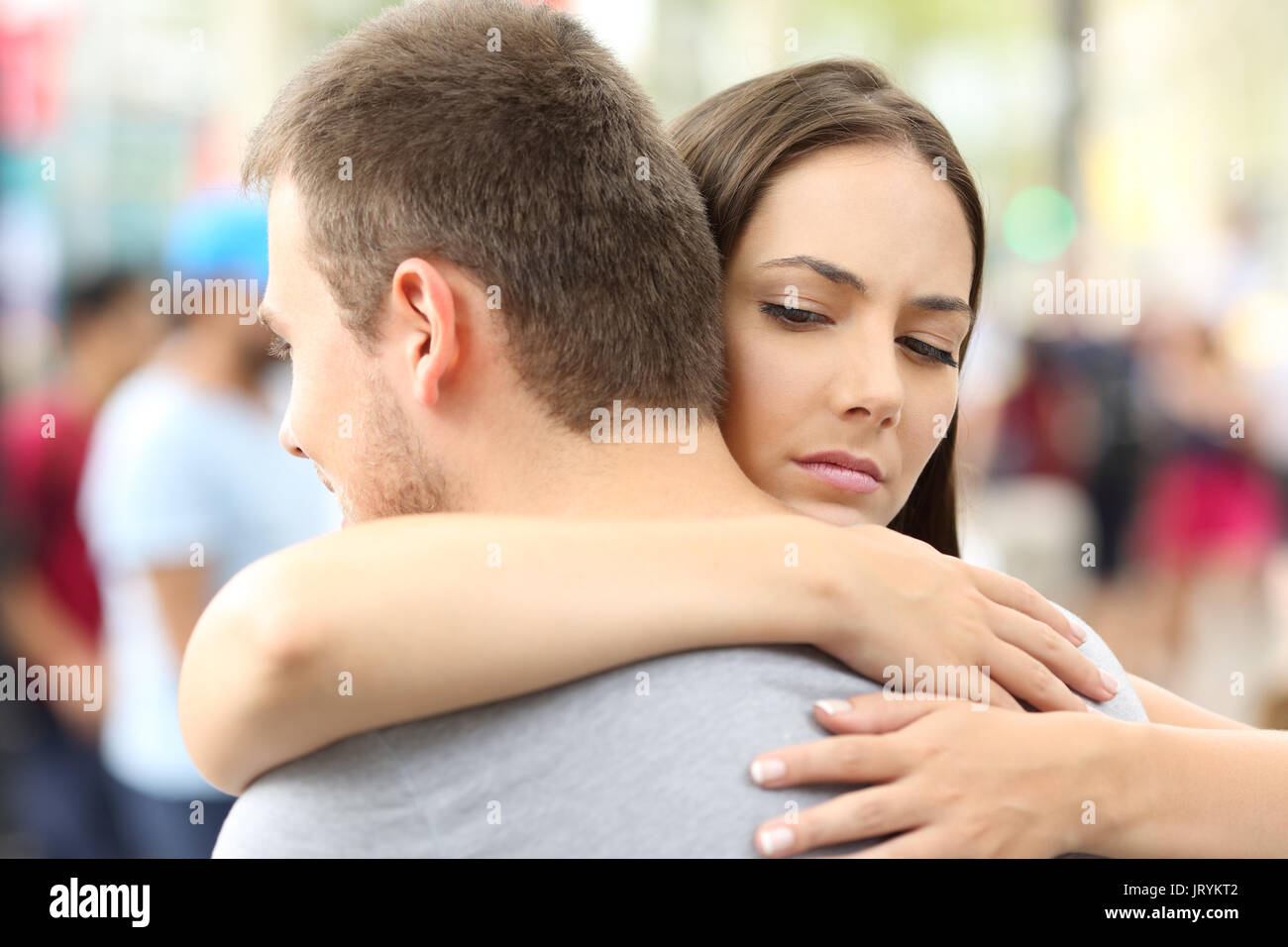 Discontent girlfriend hugging her partner on the street - Stock Image