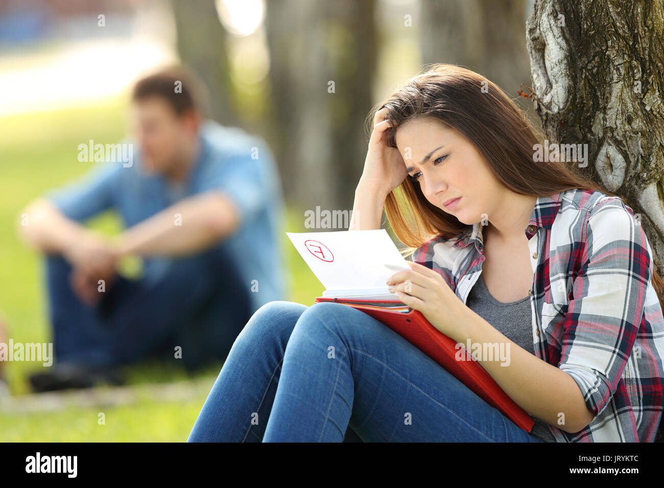 Single sad student looking at failed exam sitting on the grass in a park with unfocused people in the background - Stock Image