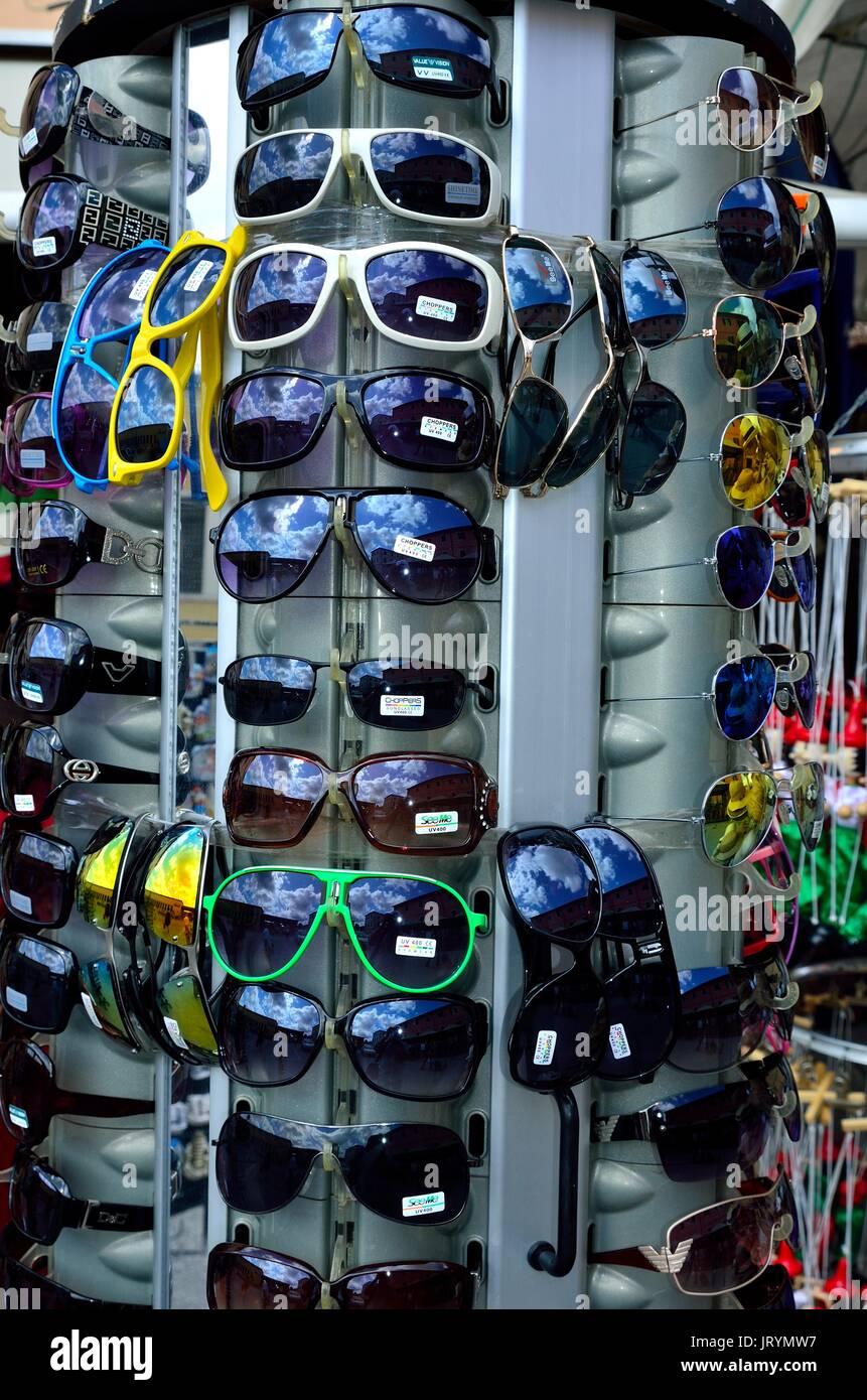 Reflection of Blue Sky in bright and colorful retro style sunglasses, for ladies and gentlemen, displayed for sale at a shop, Pisa, Italy, Europe - Stock Image